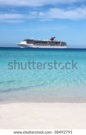 Looking at a cruise ship in the clear blue Caribbean ocean from a tropical beach - stock photo