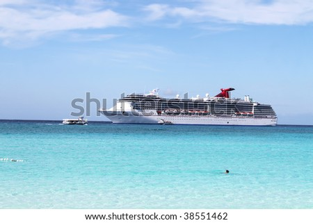 Looking at a cruise ship in the clear blue Caribbean ocean from a tropical beach
