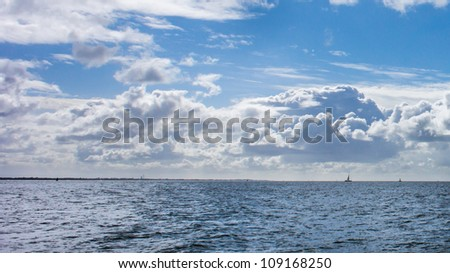 Looking at a yacht on the horizon from Calshot beach. - stock photo