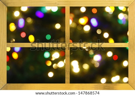 Looking at an abstract colorful christmas background through a wooden framed window - stock photo