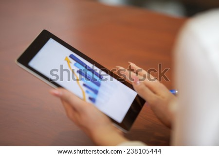 looking at business document in touchpad - stock photo