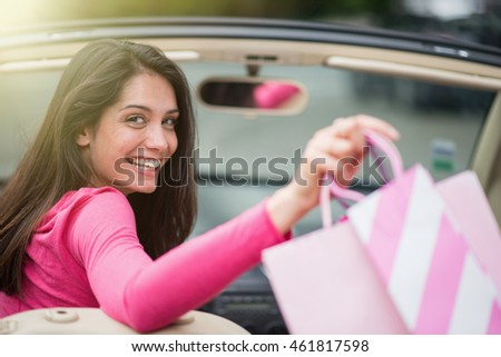 Looking at camera, a cheerful brunette woman sitting in her convertible car and depositing shopping bags on the back seat. Shot with flare