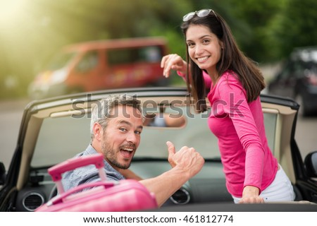 Looking at camera, a cheerful couple going away for the weekend in their convertible car, there is luggage on the back seat, the man has grey hair,  the brunette woman is standing in the vehicle.