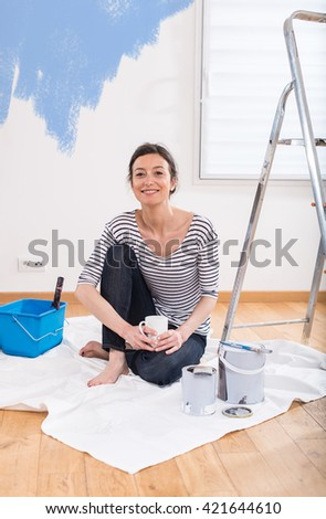 looking at camera, a cheerful woman painting her new apartment, takes a break with a coffee - stock photo