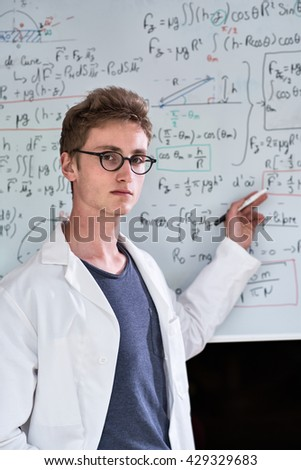 Looking at camera, a handsome young student in white coat, with glasses, posing in front of a white board filled with mathematical calculation