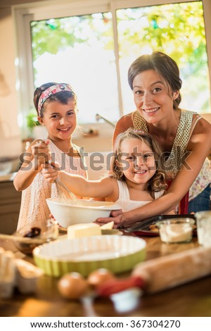 Looking at camera, a mom is cooking with her two daughters of four and seven years old. They are smiling, wearing casual clothes. The sisters are mixing the ingredients in a large bowl with a whisk. - stock photo