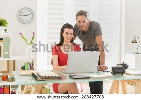 Looking at camera, at office, business team examining a project together on a laptop, the office is modern and bright - stock photo