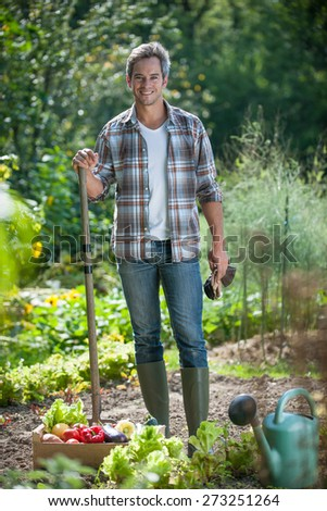 looking at camera, gardener standing in his garden, crate filled with vegetables at his feet - stock photo