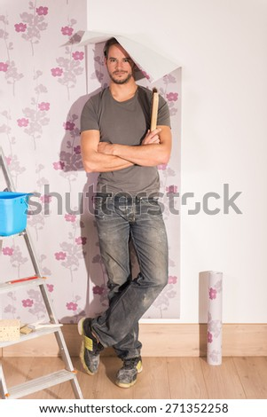 looking at camera, humorous handyman posing wallpaper, poses with his tools and a piece of wallpaper falling on his head - stock photo