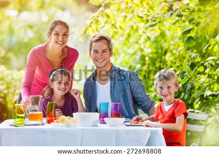 looking at camera, lovely family lunch in their garden on a sunny day, Mum is serving some apple juice, colors are bright - stock photo