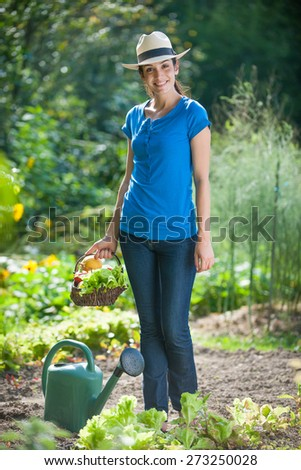 looking at camera, standing in her garden, a young woman a basket of vegetables by hand  - stock photo