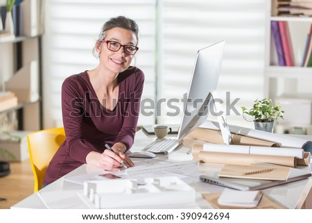 Looking at camera. Young female architect sitting at office, working on blueprints for a new building project. She wears eyeglasses. - stock photo