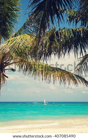 Looking at the beautiful tropical beach and the blue ocean through palm trees. Vintage post processed. Fashion, travel, summer, vacation and tropical beach concept. Punta Cana, Dominican Republic - stock photo