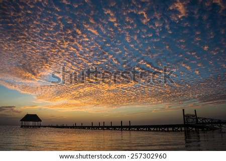 looking at the sun going down on a wooden pier with a hut. - stock photo