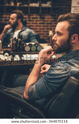 Looking awesome as ever. Side view of handsome young bearded man looking away and keeping hand on chin while sitting in chair at barbershop - stock photo