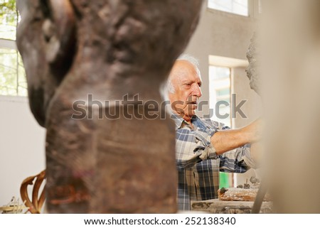 Looking behind the statues at the working sculptor - stock photo