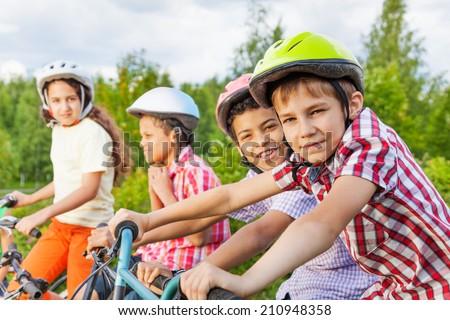Looking boy in helmet with his friends behind - stock photo