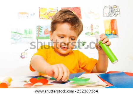 Looking cute boy crafting while holding glue - stock photo
