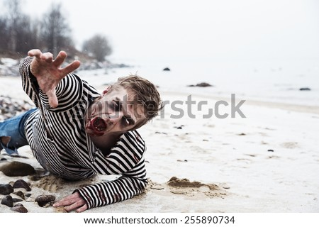 Looking dead man crawling on the seaside