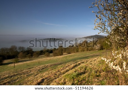 Looking down a hill towards some morning mist in the trees.  Taken early morning at Newlands Corner near Guildford in Surrey, UK. - stock photo