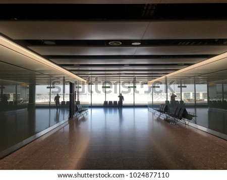 Looking down a long hallway of an airport terminal at the silhouette of a man talking on the phone. Large windows and reflections on the floor of an airport, dramatic lighting, one person.