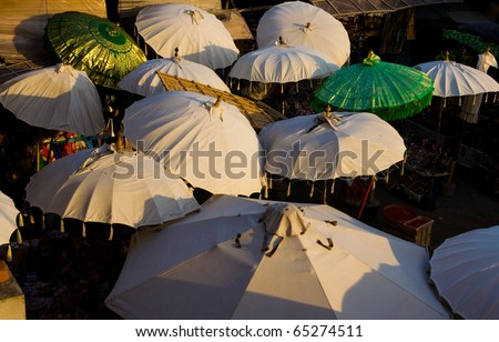 Looking down above many oversize umbrellas providing evening shade at the market stalls in Ubud, Bali, Indonesia. Horizontal