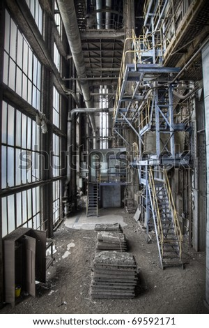 Looking down at a factory hall. Shot taken at an abandoned factory. - stock photo