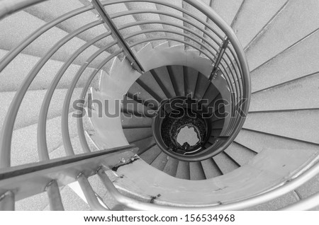Looking down at a spiral staircase, black and white photo. - stock photo