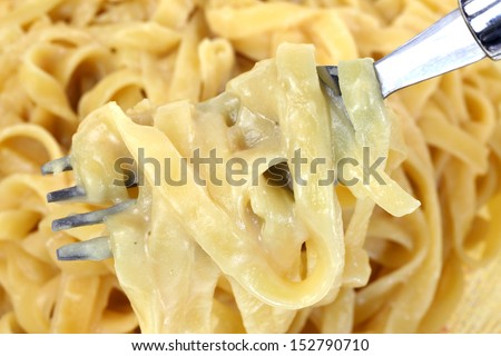 Looking down at fettuccine alfredo pasta on a fork. - stock photo