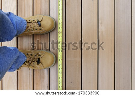 Looking Down at Worker and Tape Measure - stock photo