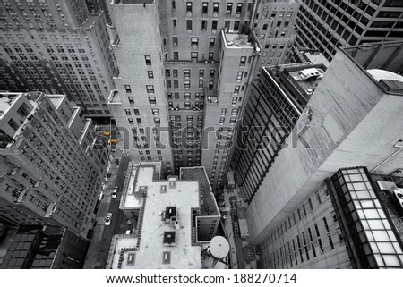 Looking down at yellow taxis, cabs, in the streets of New York, USA, as small colorful dots in black and white ultra wide angle composition of tall skyscrapers and apartment buildings - stock photo