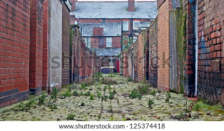 Looking down inner city cobblestone alley - stock photo