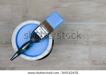 Looking down on a can of Blue Paint with a loaded brush stood on a shabby style wood floor - stock photo