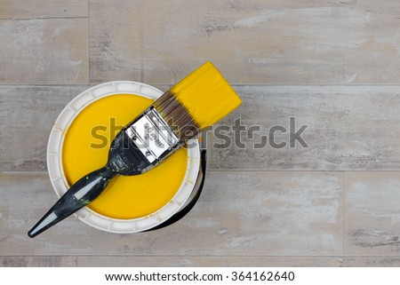 Looking down on a can of Bright Yellow Paint with a loaded brush stood on a shabby style wood floor - stock photo