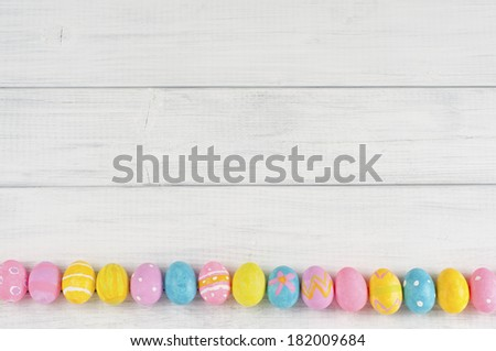 Looking Down on a Row of Easter Eggs in a row along bottom of rustic white wood board background with room or space above for copy, text, words.  Horizontal - stock photo