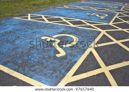 Looking down on blue and yellow disabled parking pays in a car park. - stock photo
