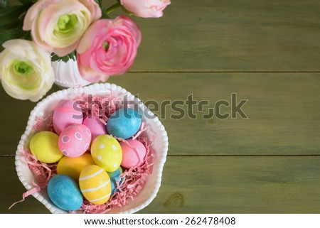Looking Down on Pretty, Colorful Easter Eggs in a Bowl with Flowers in a Vase on a Rustic Green Painted Wood Board Background with Room or Space for Copy, Text, or Your Words.  Horizontal above view - stock photo