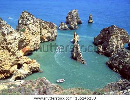 Looking down on rocky eroded scenic coastline with small boats Algarve Portugal - stock photo