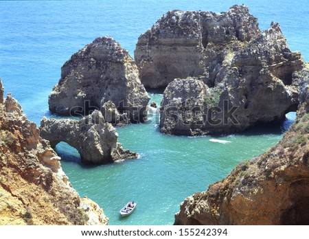 Looking down on the geology of rocky eroded scenic coastline with a small boat Algarve Portugal - stock photo