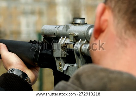 Looking down the barrel of a russian sniper rifle being held by a non identifiable man dressed in casual wear - stock photo