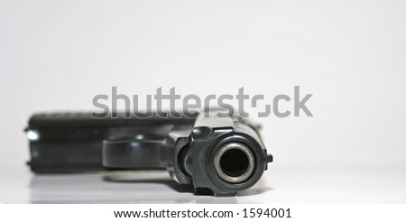 Looking down the barrel of a semi automatic handgun with only the end of the barrel in focus - stock photo