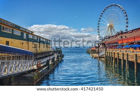 Looking Down the Docks of the Pier District in Seattle, Washington with the Great Wheel in the Distance - stock photo