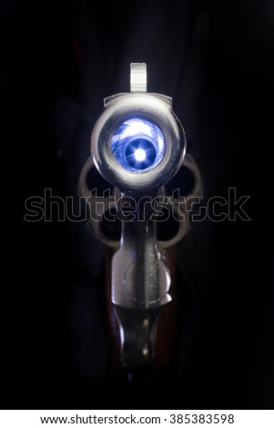 Looking down the muzzle of a .38 caliber nickel revolver. - stock photo