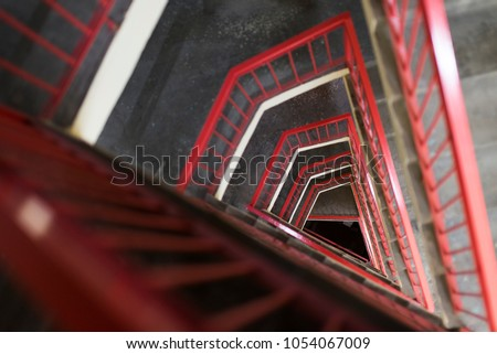 Looking downside from triangular Stairs with red railings