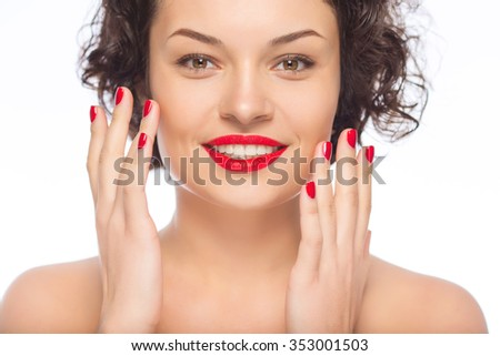 Looking fabulous. Young attractive lady looks happy with herself while smiling and showing her perfect manicure.