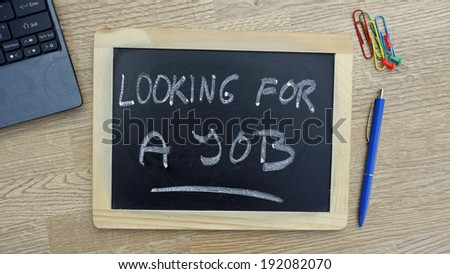 Looking for a job written on a chalkboard at the office - stock photo