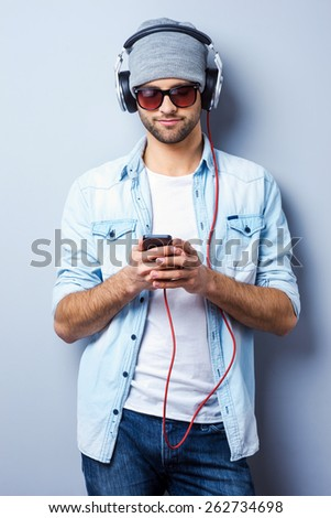 Looking for his favorite song. Handsome young stylish man in headphones holding MP3 Player and looking at it while standing against grey background - stock photo