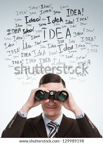Looking for Ideas concept. Young business man standing on gray background with with binoculars idea signs in front - stock photo