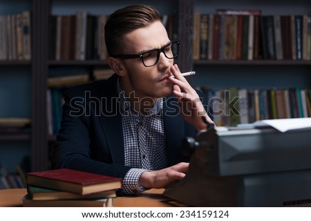 Looking for inspiration. Confident young author working at the typewriter and smoking cigarette while sitting at his working place with bookshelf in the background  - stock photo