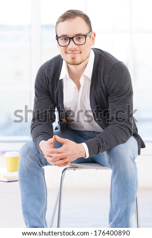 Looking for inspiration. Thoughtful young man in shirt looking at camera and smiling while sitting on the chair - stock photo